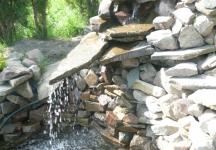 Wodospad w oczku wodnym w realizacji firmy Aloes